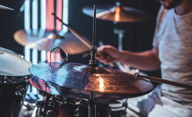 Close de um prato de bateria enquanto o baterista toca.