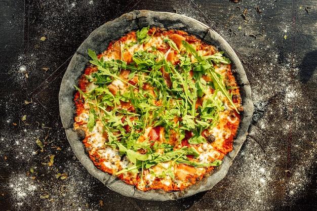 Close de um prato de pizza com rúcula na mesa preta