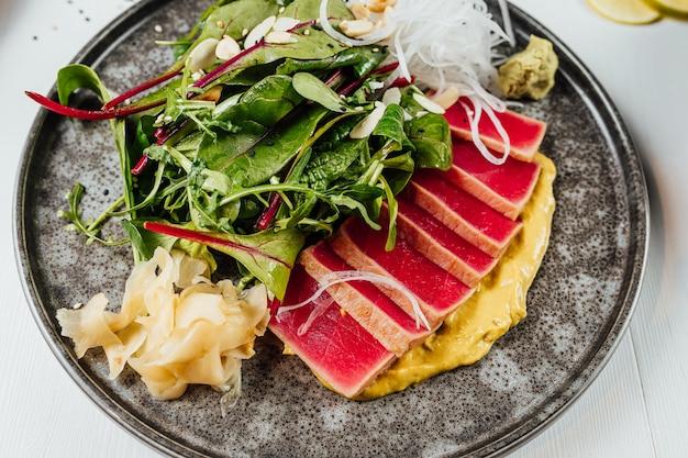Close de um prato de sushi com legumes frescos na mesa branca