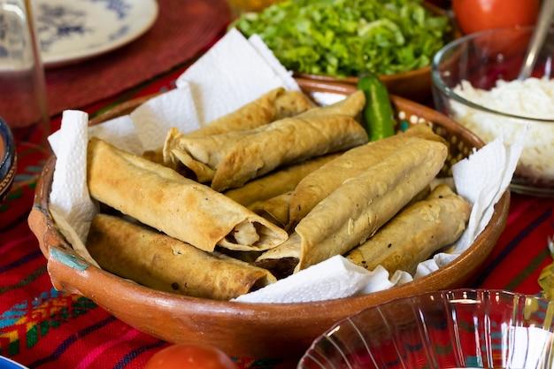 Close de um prato de tacos mexicanos fritos em uma mesa