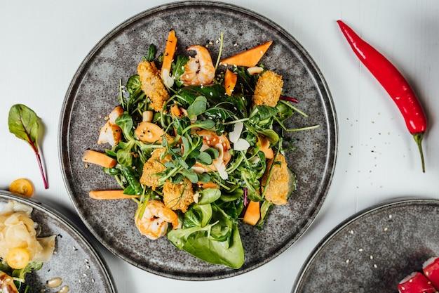 Close de um prato de tempura com legumes frescos na mesa branca