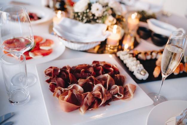 Close de um prato quadrado branco com presunto em uma mesa servida festivamente com conjunto de sushi