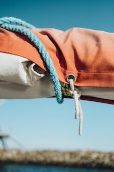 Close de um prendedor laranja e branco amarrado por cordas azuis