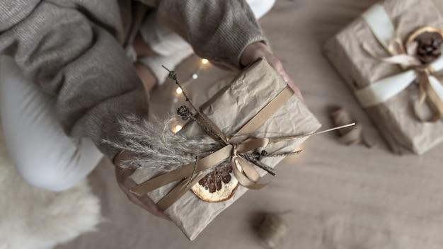 Close de um presente de natal, decorado com flores secas e uma laranja seca, embrulhado em papel artesanal.