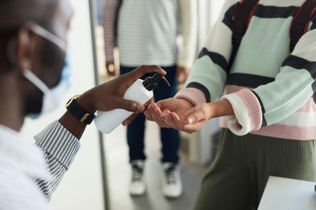 Close de um professor ajudando crianças a higienizar as mãos ao entrar na sala de aula na escola, medidas de segurança ambiciosas
