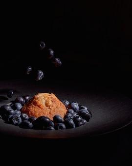 Close de um queque com mirtilos em uma placa preta