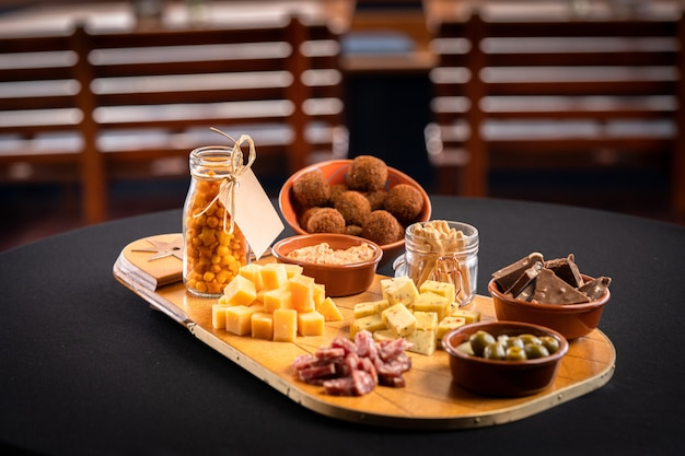 Close de um rastro de madeira com variedade de queijo, azeitonas verdes, barras de chocolate