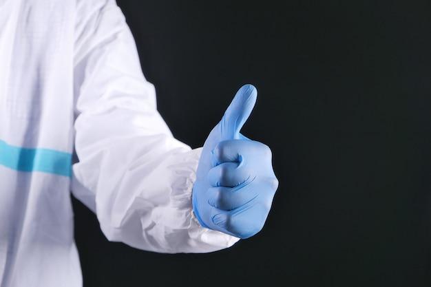 Close de um reboque de pessoas com luvas médicas mostrando o polegar para cima