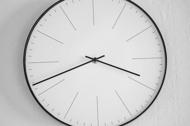 Close de um relógio branco e preto em uma parede branca - o conceito de tempo