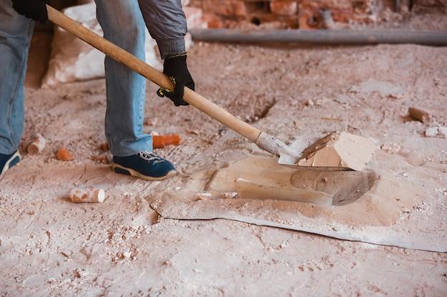 Close de um reparador em um construtor profissional uniforme, trabalhando com equipamentos de construção