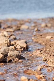 Close de um riacho fluindo na areia e pedras na costa