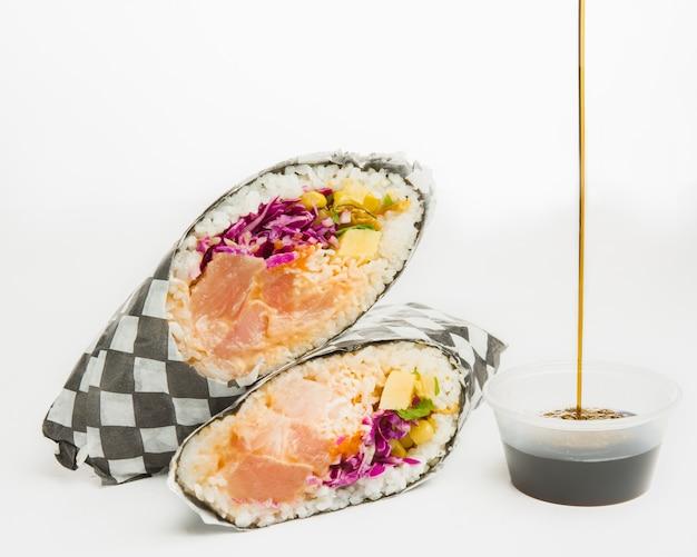 Close de um rolo de califórnia com repolho roxo, salmão, milho e legumes fatiados