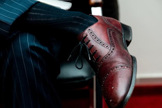 Close de um sapato de couro em uma pessoa sentada com as pernas cruzadas sob as luzes