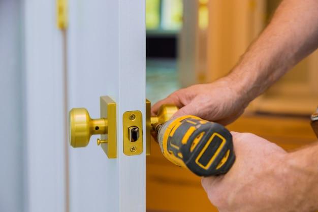 Close de um serralheiro profissional instalando ou novo bloqueio em uma porta de casa com chave de fenda