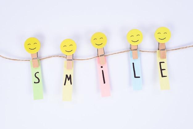 Close de um smiley brilhante bom e alegre segurando papéis adesivos com uma parede branca isolada de palavra de sorriso