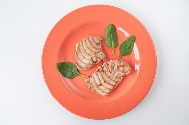 Close de um suculento e delicioso bife de atum grelhado em um prato brilhante