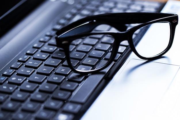 Close de um teclado e óculos