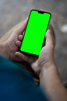 Close de um telefone com uma tela verde nas mãos masculinas, um homem com um smartphone nas mãos