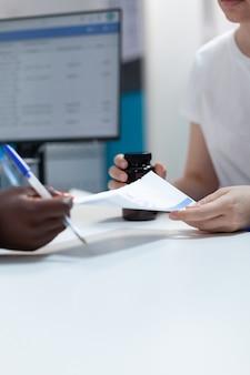 Close de um terapeuta afro-americano dando prescrição de antibióticos ao paciente