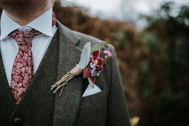 Close de um terno de noivo com flores e gravata estampada em vermelho com árvores ao fundo