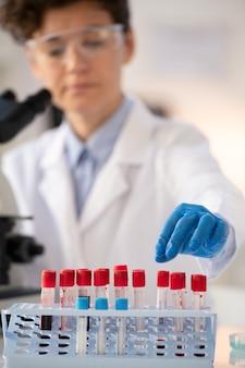 Close de um trabalhador de laboratório com luvas azuis separando amostras de sangue na prateleira enquanto faz os testes