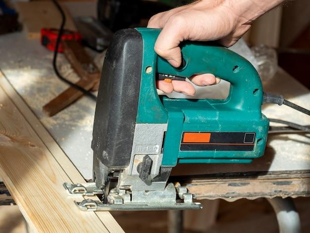 Close de um trabalhador serrando uma tábua de madeira com uma serra elétrica