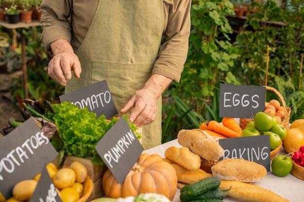 Close de um vendedor de uma fazenda irreconhecível com avental colocando placas no balcão de comida