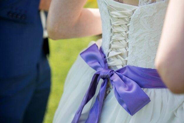 Close de um vestido de noiva com um grande laço de seda roxa