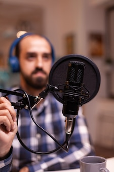 Close de um vlogger segurando o microfone enquanto fala durante uma entrevista online