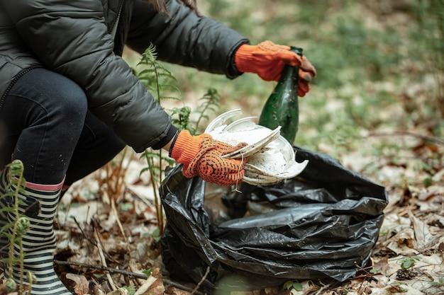 Close de um voluntário limpa a natureza de vidro, plástico e outros detritos