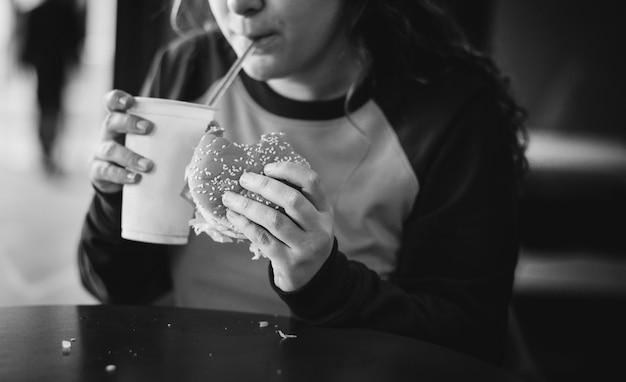 Close de uma adolescente comendo hambúrguer