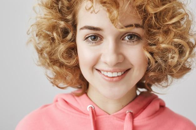 Close de uma adolescente feliz e sorridente com cabelos cacheados