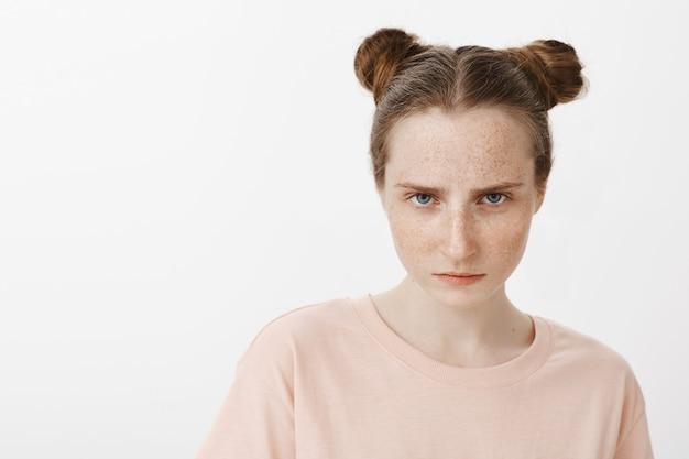 Close de uma adolescente focada posando contra a parede branca