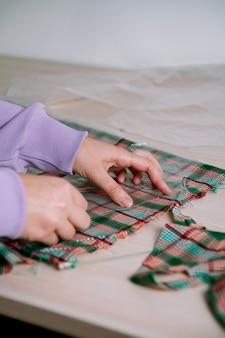 Close de uma alfaiate feminina recortando um tecido xadrez com um padrão de papel para distinguir uma camisa, foco seletivo