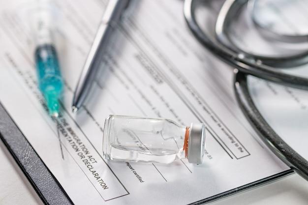 Close de uma ampola e uma seringa de agulha em um documento com um estetoscópio