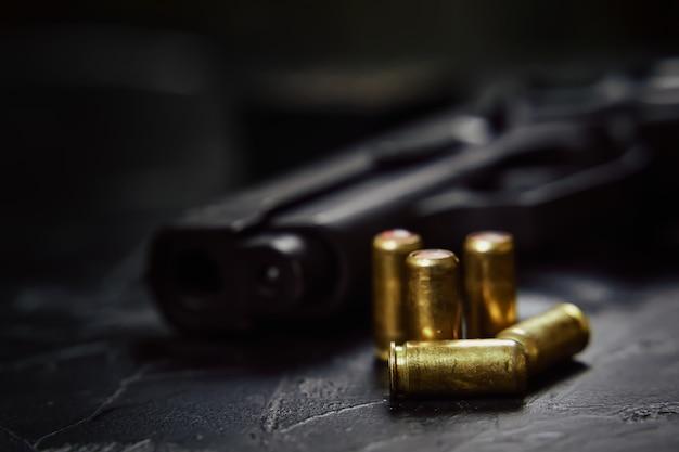 Close de uma arma e balas na pistola de mesa de concreto para defesa ou ataque com armas de fogo e munições