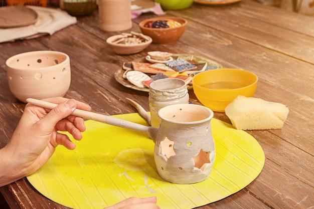 Close de uma artista feminina pinta um castiçal de argila cinza em uma mesa de madeira