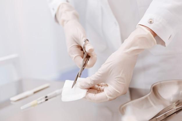 Close de uma bandagem sendo cortada em vários pedaços enquanto é segurada por um bom médico profissional