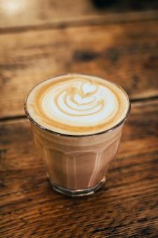 Close de uma bebida de chocolate espumosa em um copo sobre uma mesa de madeira