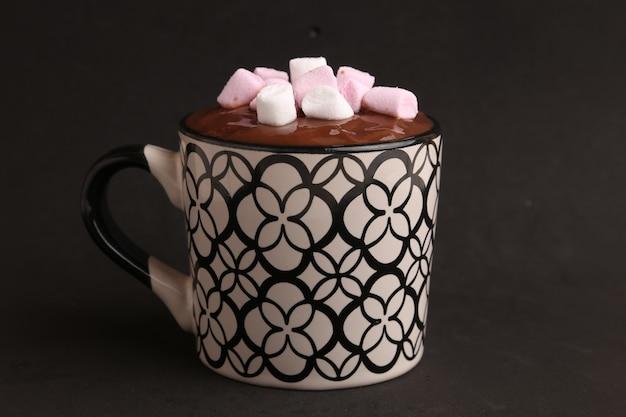 Close de uma bebida de chocolate quente com marshmallows por cima e um fundo preto