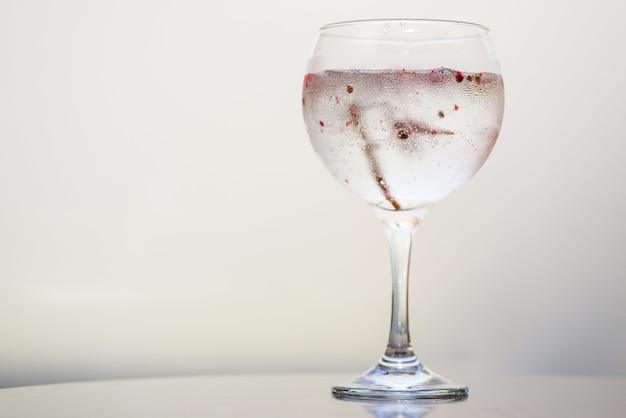 Close de uma bebida em um copo sob as luzes contra um fundo branco