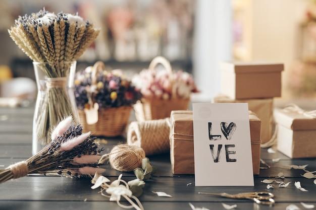 Close de uma bela composição de outono com cartão romântico, flores secas, caixas de presente em papel kraft na mesa