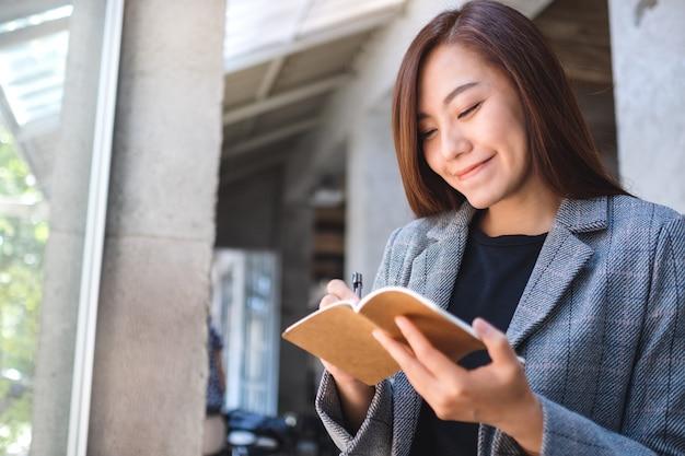 Close de uma bela empresária asiática segurando e escrevendo em um caderno