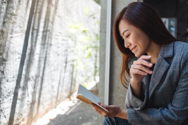 Close de uma bela empresária asiática segurando e olhando para um notebook