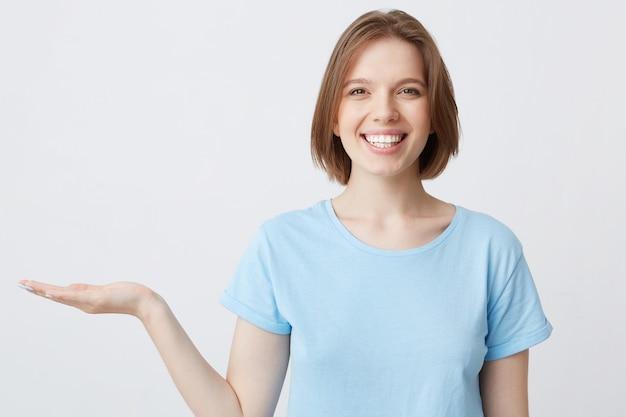 Close de uma bela jovem alegre em azul segurando copyspace na palma da mão e rindo