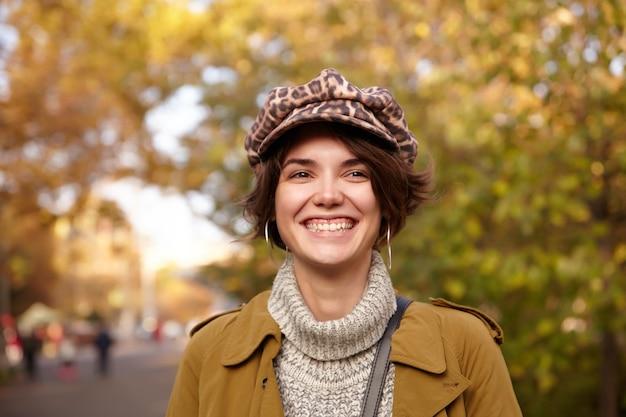 Close de uma bela jovem atraente de cabelos castanhos com maquiagem natural, rindo alegremente enquanto caminhava pelo parque em um dia quente de outono, vestida com roupas elegantes
