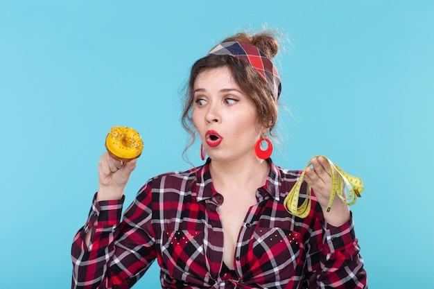 Close de uma bela jovem chocada e chateada segurando uma fita métrica e um donut