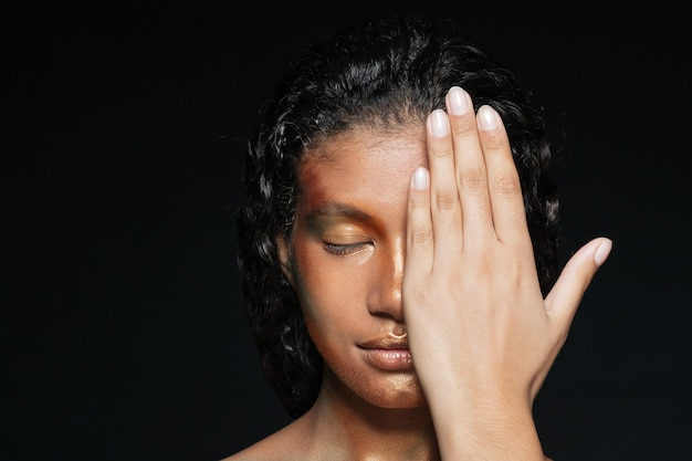 Close de uma bela jovem cobrindo metade do rosto com a mão sobre o preto