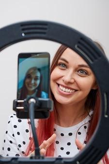 Close de uma blogueira, com uma camisa branca com bolinhas, faz uma transmissão ao vivo, usando um smartphone, uma luminária de anel.
