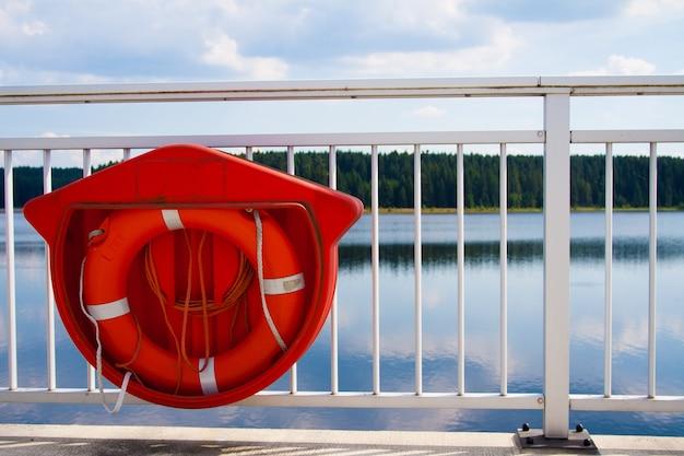 Close de uma boia salva-vidas vermelha pendurada na grade branca de uma ponte